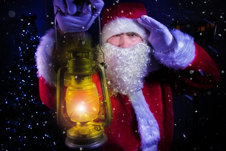 Young santa clause, carrying lantern looks through blizard of snow with christmas tree and street lamp in background Stock Photo