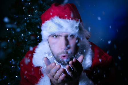 Good looking male Santa blowing snow at lens Stock Photo