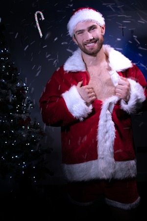 Good looking male santa pulls open his jacket revealing his chest with christmas try in background