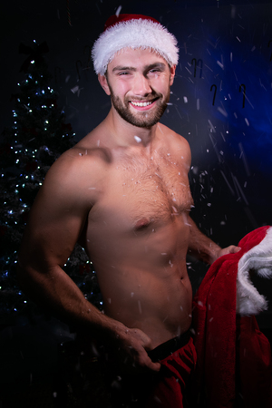 Good looking shirtless santa with pecs is smiling holding his jacket with Christmas tree in background
