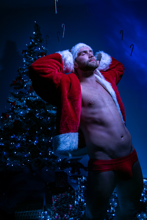 Good looking male santa with open jacket and red underwear stretching in front of christmas tree