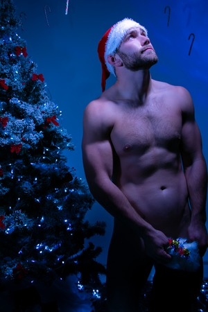 Hunky nude male santa wearing just a hat holding stocking full of candy as he looked up at the moonlight Stock Photo