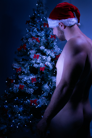 Good looking male santa with nude rear and hat decorating christmas tree