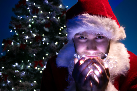 Handsome male santa smiling and holding lights in his hand with christmas tree in background