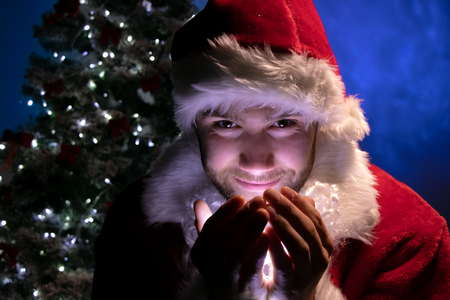 Handsome male santa smiling and holding lights in his hands and looking at camera with christmas tree in background