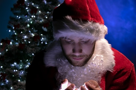 Handsome male santa with beard looking down at lights in his hands with christmas tree in background Imagens - 112529608
