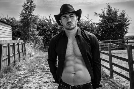 Sexy, handsome, hunky cowboy with hat open shirt and sixpack abs looking at camera