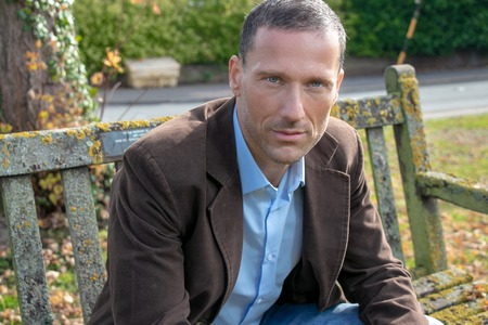 Handsome middle aged man wearing shirt and jacket sitting on park bench Stock Photo
