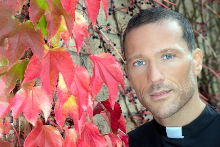 Good looking priest with visible collar poses for portrait next to red virginia creeper ivy
