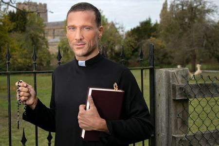 Knappe priester die naast ijzeren poort staat met bijbel met veld, alpaca's en kerk op de achtergrond