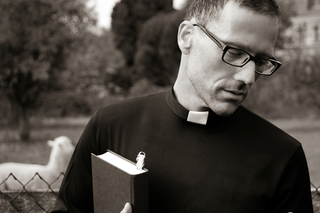 Handsome priest wearing glasses and holding bible with alpaca in field behind him