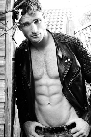 Handsome blonde man with open leather jacket revealing sixpack abs and looking at camera Stock Photo