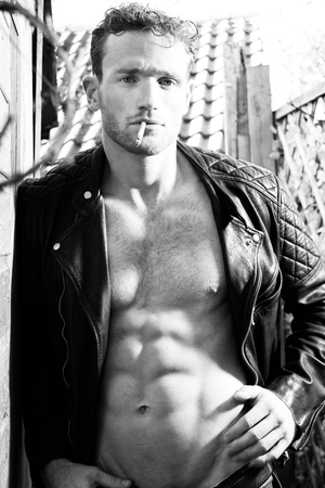 Handsome blonde man with open leather jacket revealing sixpack abs smoking cigarette and looking at camera Stock Photo