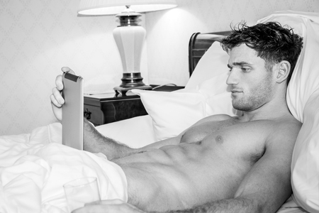 Handsome, sexy man with six pack abs lying in bed using digital tablet