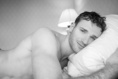 Black and white picture of handsome man lying on hotel room bed sheets