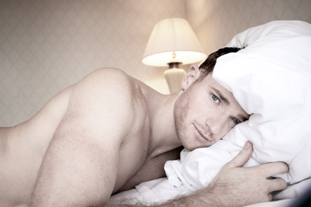 Handsome muscular  men with blue eyes lying on hotel bed sheets looking at camera Stock Photo