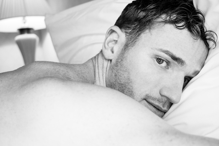 Sexy handsome shirtless man with beard lying on hotel bed pillow and looking at camera Stock Photo