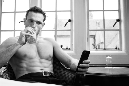 Handsome shirtless man with muscular pecs and six pack abs using mobile phone and drinking juice Stock Photo