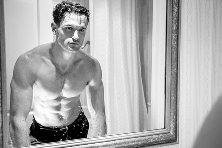 Handsome shirtless man with muscular body and sixpack abs looking at his reflection in bathroom mirror