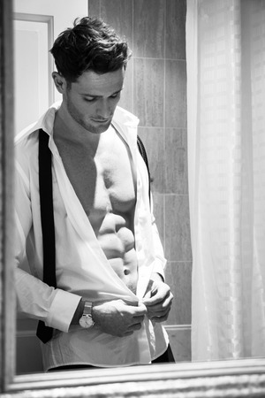 Handsome man with muscular body unbuttoning shirt to reveal sixpack abs reflection in bathroom mirror