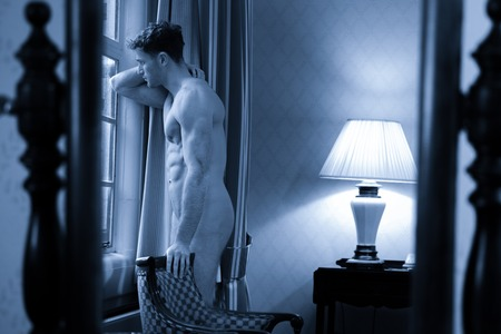 Black and white portrait of handsome man with muscular body standing by large window of hotel room