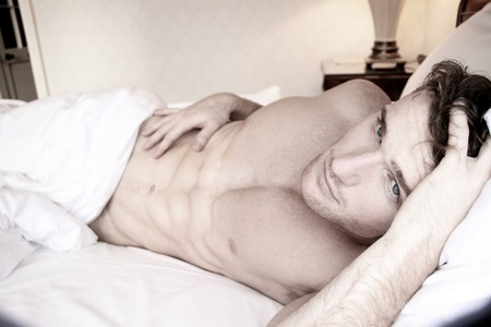 Handsome man with six pack abs and blue eyes lying in hotel room bed Stock Photo