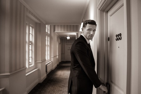 Sepia image of handsome man in suit in hotel corridor using key card to open room door Imagens - 115725005
