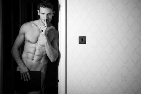 Naked man with muscular body standing in doorway covering himself with book while holding a finger to his lips Stock Photo