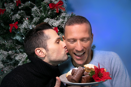 Male gay couple kissing and laughing in front of christmas tree with plate of cakes Imagens - 115725083
