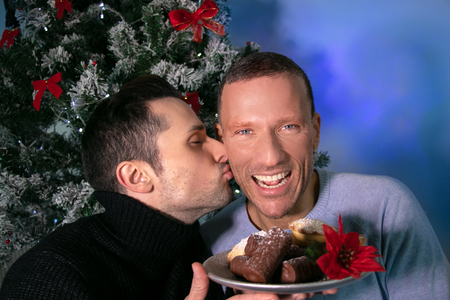 Male gay couple kissing and laughing in front of christmas tree with plate of cakes Imagens - 115725088