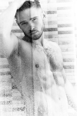Attractive naked man with beard in shower looking at camera