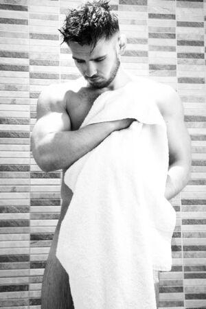 Good looking man towelling himself dry in shower 写真素材