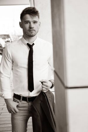 Portrait of handsome man wearing shirt and tie and holding jacket.