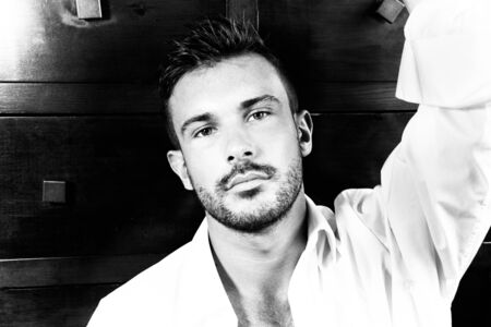Portrait of good looking man with beard and open shirt looking at camera