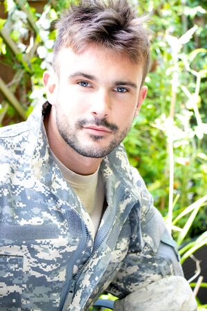 Portrait of attractive male soldier wearing camouflage uniform looking at camera