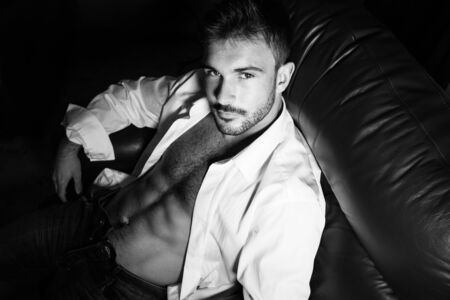 Portrait of attractive young man with beard and open shirt revealing sixpack abs, sitting in leather armchair Фото со стока