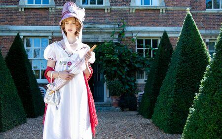 Beautiful woman in vintage Georgian dress and bonnet standing in garden of stately home Standard-Bild