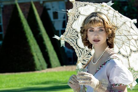 Schöne Dame in Regentschaftskleidung, die auf dem Rasen vor dem Herrenhaus sitzt, Sonnenschirm hält und Sekt trinkt