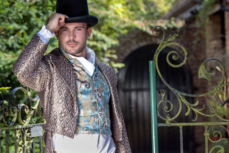 Ritratto di un bel gentiluomo vestito in costume vintage, che tiene in mano un cappello a cilindro nel maestoso cortile di casa
