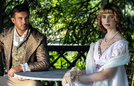 Handsome young couple in vintage clothing sit in gazebo. The female is looking at camera as her companion looks at her.