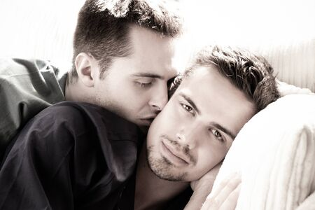 Handsome gay man with goatee looks at camera as his partner or husband kisses his cheek Фото со стока