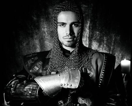 Portrait of brave knight in suit of armour looking at camera with candles in background Stock Photo