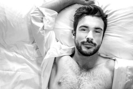 Portrait of handsome hairy muscular man with beard and open white shirt, looking up from bed at camera 版權商用圖片