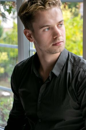 Portrait of handsome man with blonde hair and black shirt sitting in window