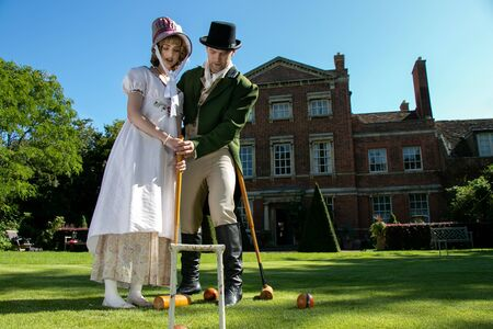 Handsome man and beautiful woman dressed in vintage clothing on lawn in front of stately home, playing croquet