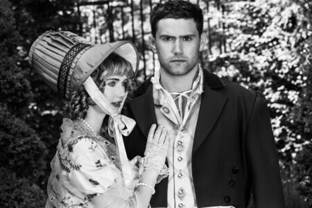 Portrait of attractive couple dressed in vintage clothing with handsome man looking at camera as his partner looks on