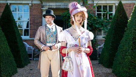 Handsome man and beautiful woman dressed in vintage clothing, standing in front of stately home Standard-Bild