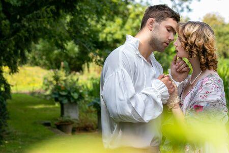 Junges, gutaussehendes Paar in Vintage-Kostüm, das am Ufer des Flusses und unter Bäumen steht und sich küssen.