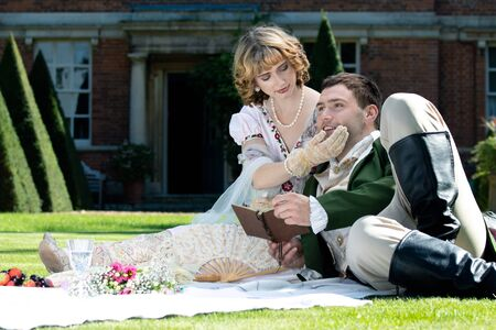 Young lovers dressed in vintage clothing sitting on picnic blanket. Gentleman looking at his partner while holding book
