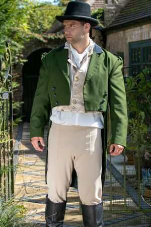 Portrait of handsome gentleman dressed in vintage costume and top hat standing in stately home courtyard Stok Fotoğraf